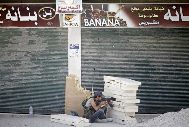 A Free Syrian Army fighter aims his rifle during heavy fighting in Salaheddine neighborhood of central Aleppo
